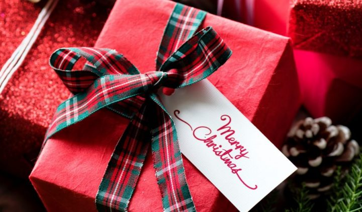 christmas present in red wrapping paper with tartan ribbon and merry christmas tag