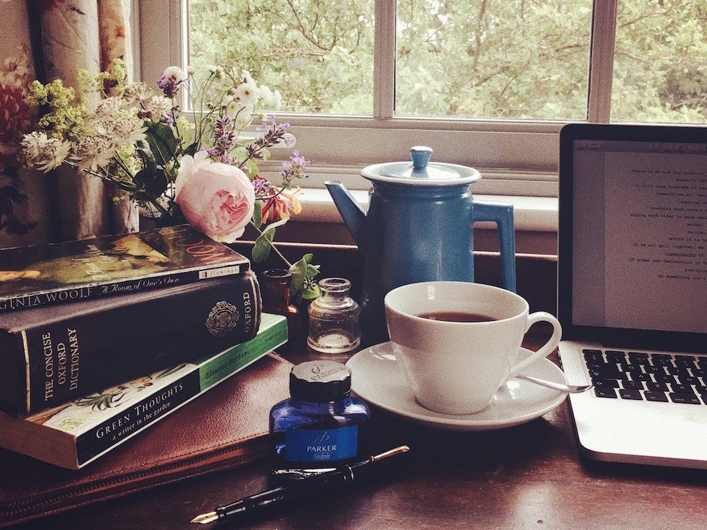 writers retreat MacBook blue teapot white cup of tea saucer stack of books flowers vase