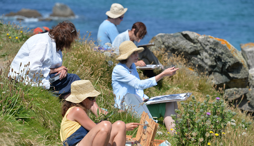 women sitting of cliff edge in sun hats painting on clipboards sea in background