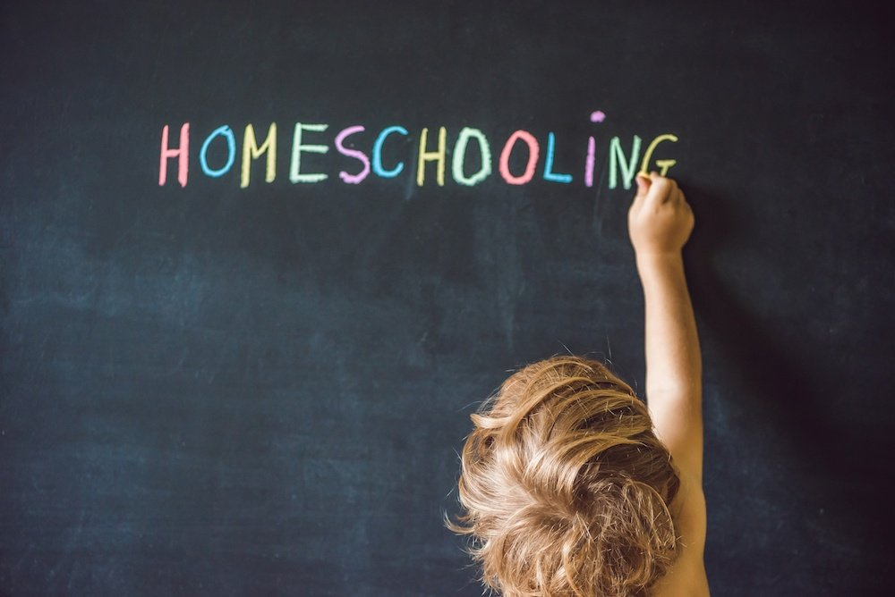 child writing HomeSchooling on a blackboard in chalk