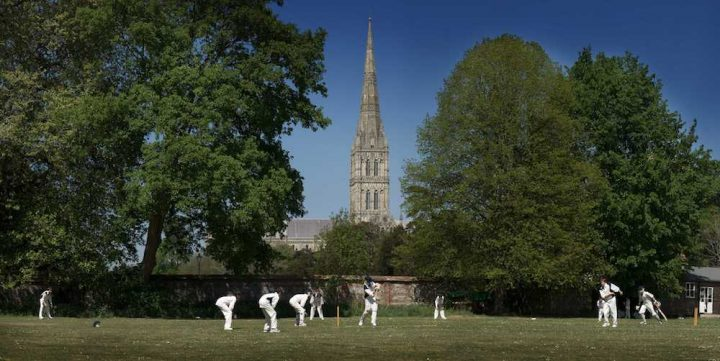 boys playing cricket with Salisbury Cathedral in background