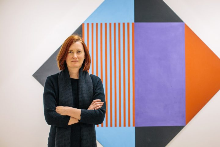 woman short auburn hair crossed arms painting purple black blue orange squares triangle white wall