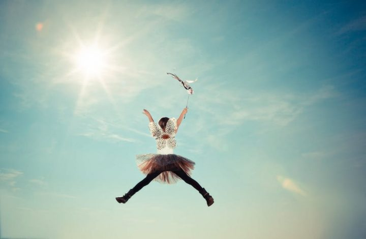 little girl in tutu fairy wings wand in hand jumping in air blue skies bright sun