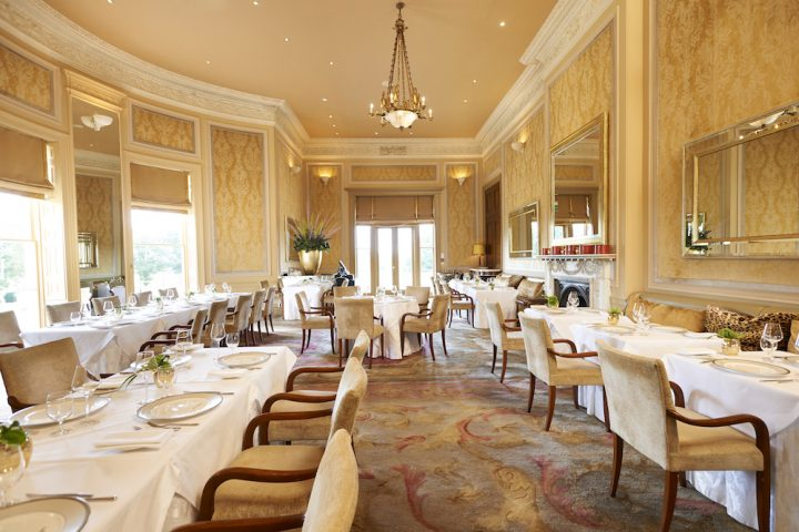 dining area white chairs multicoloured carpet white table clothes chandelier golden walls