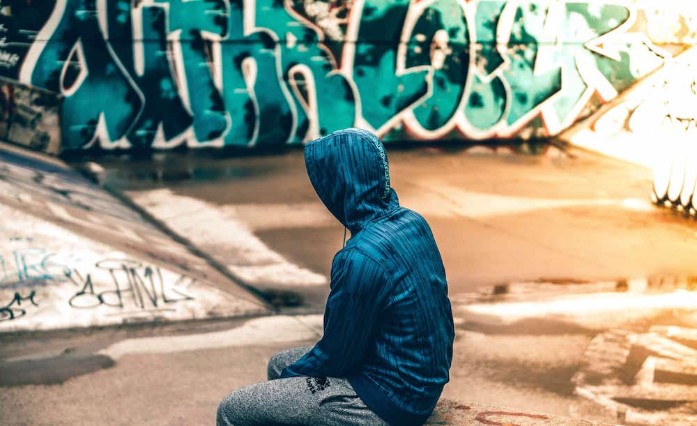 child in skate park wearing a hoodie with graffiti in the background