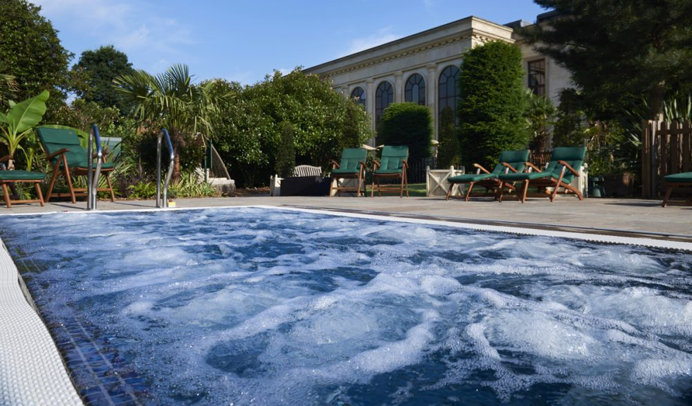 bubbling hot tub jacussi outside with large paladian spa building in the background