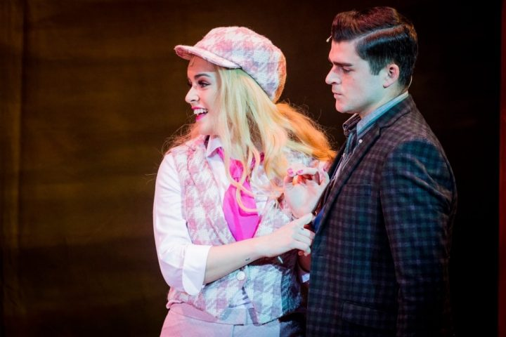 legally blonde uk tour blonde lady in pink chequered waistcoat and hat gripping a mans suit jacket