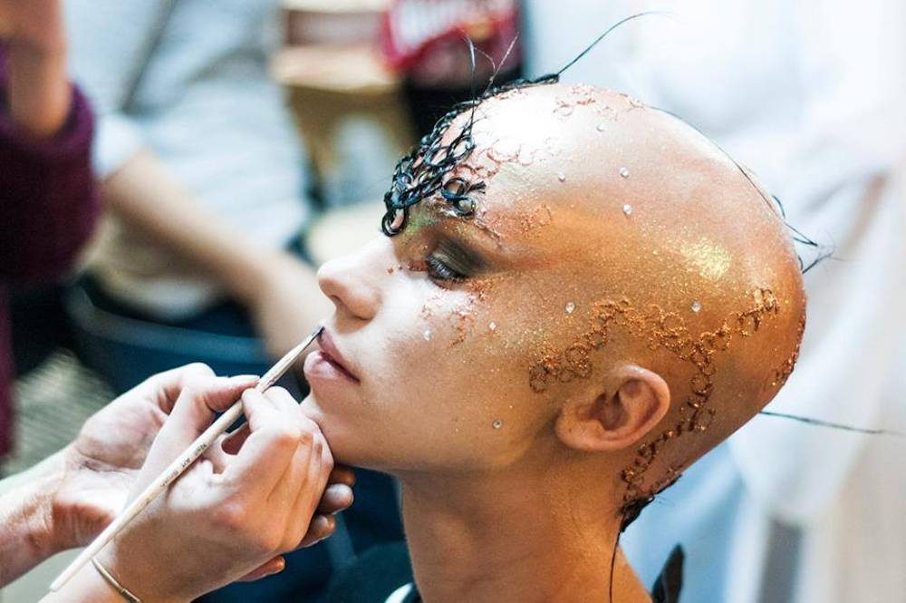 bald woman with fantasy make up on and someone putting a brush on her lip