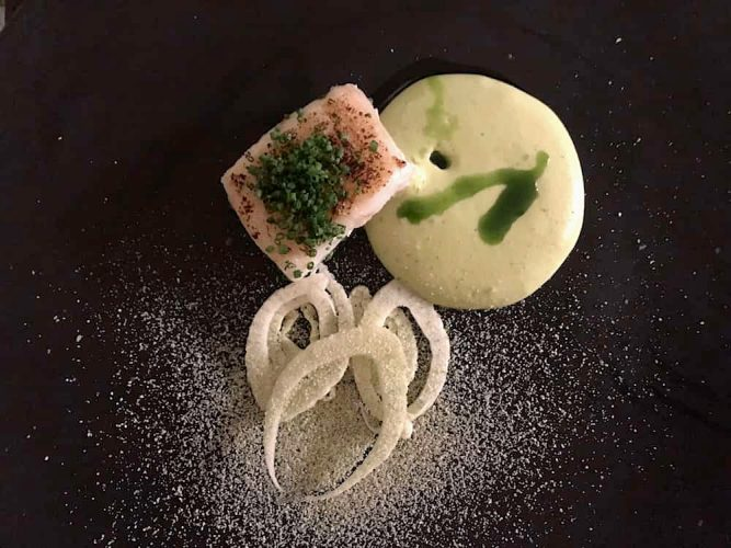 black plate cooked cod piece green curry sauce fennel rings white dust sprinkling