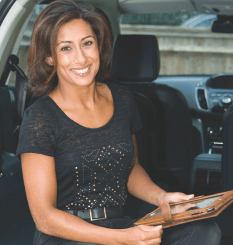 sari khan in black t-shirt smiling in the back of a car