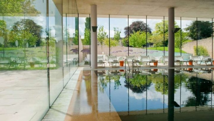 Cowley manor spa indoor pool glass walls reflection in water tall pillars