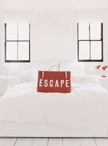 red escape bag on bed white room windows