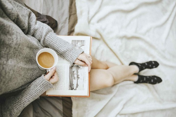 woman reading a book with a up of coffee and slouchy jumper