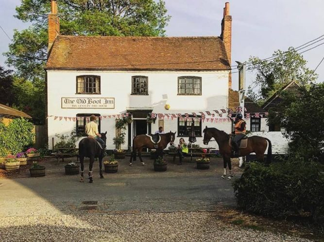 white panted exterior Old Boot Stanford Dingley pub with tiers on horseback pulling up n front for refreshments
