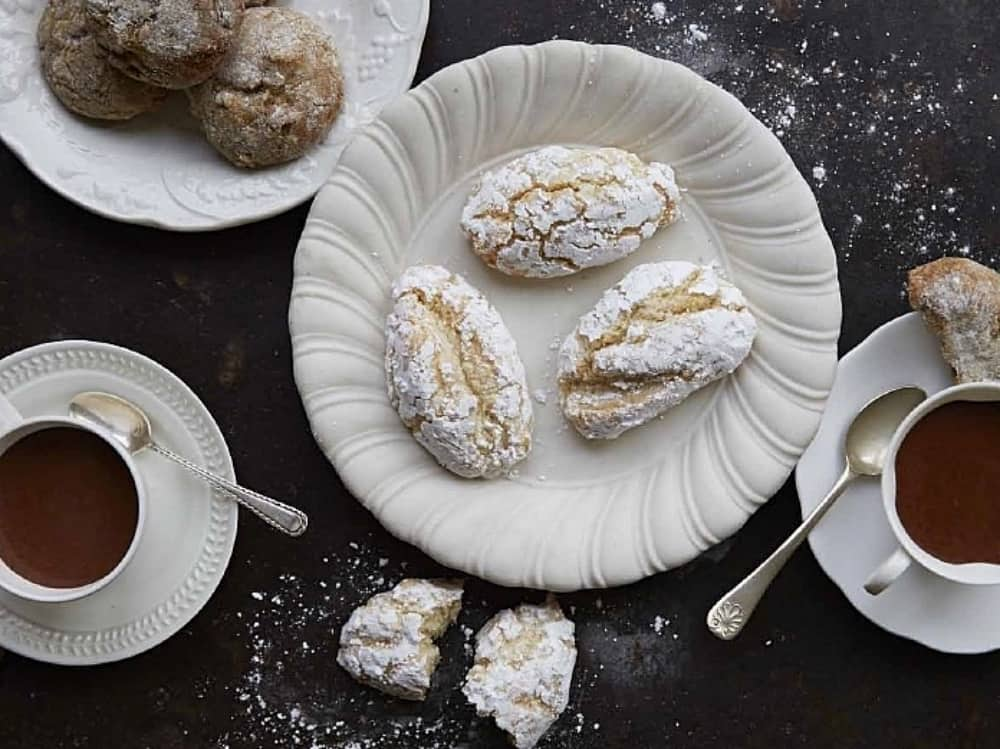 Cladesi Ricciarelli biscuits white wavy plates black worktop and two cups of coffee