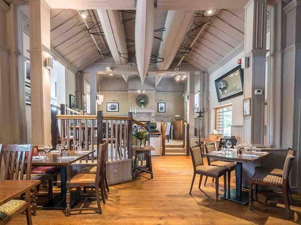 Grey walls and ring boats fixed to ceiling wooden floor and dark wood tables and chairs