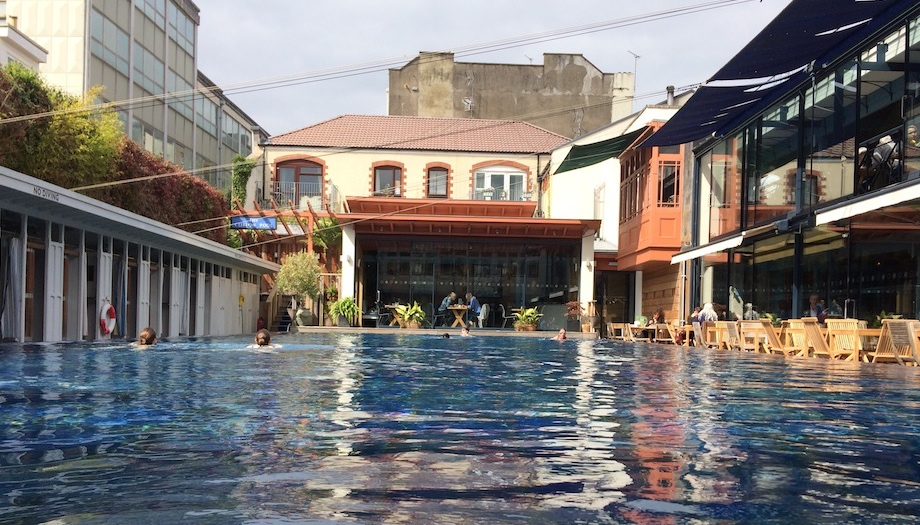 infinity swimming pool surrounded by changing cubicles, and cafe with tables and chairs in the city